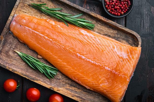 Filet de poisson rouge saumon cru frais sur des planches sombres en bois.