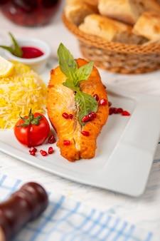 Filet de poisson de saumon blanc grillé avec garniture basilique, tomate et riz.