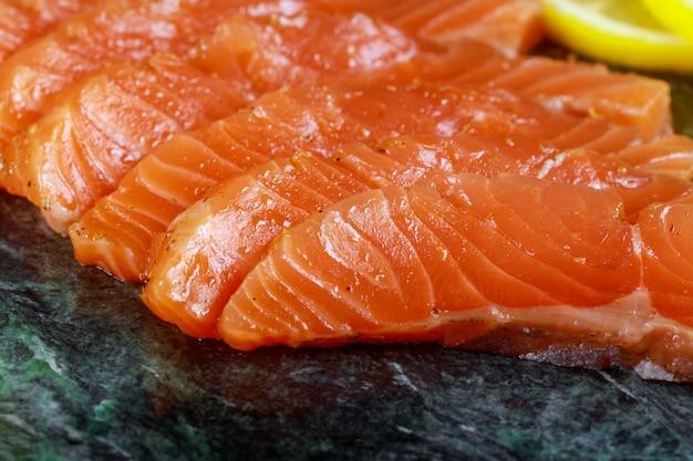 Filet de poisson de saumon non cuit à l'avocat, sur plaque de marbre, ingrédients de la vue de dessus prêt à manger