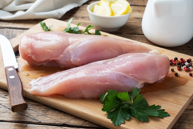 Filet de poitrine de poulet cru sur une planche à découper en bois. planche rustique en bois.