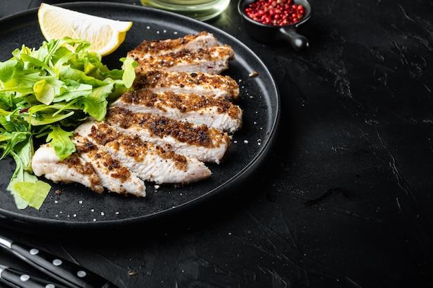 Filet de poitrine de poulet émietté, grillé, sur fond noir avec un espace réservé au texte