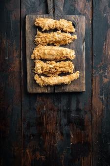 Filet de poitrine de poulet pané sur une table en bois sombre, mise à plat.