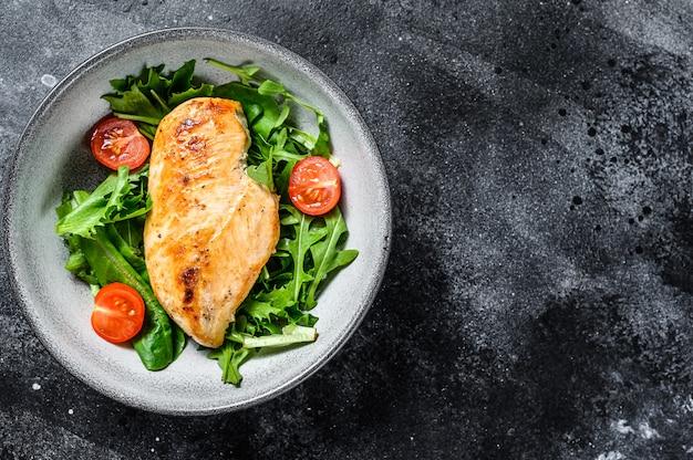 Filet de poitrine de poulet avec salade de roquette. aliments sains, régime céto, concept de régime alimentaire. fond noir. vue de dessus. espace copie