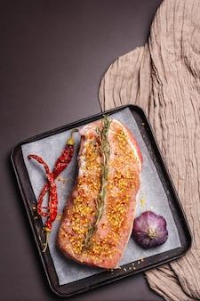 Filet de porc cru. viande fraîche avec de l'ail, du romarin et du piment rouge dans un plat allant au four