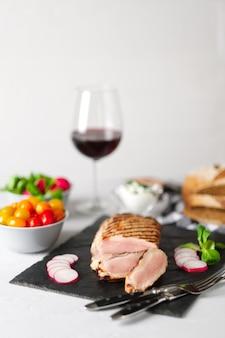 Filet de porc grillé en tranches avec tomates fraîches et radis, accompagné d'un verre de vin rouge. photo flou.