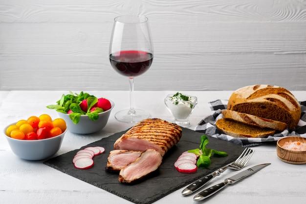 Filet de porc grillé en tranches avec tomates fraîches et radis, accompagné d'un verre de vin rouge.