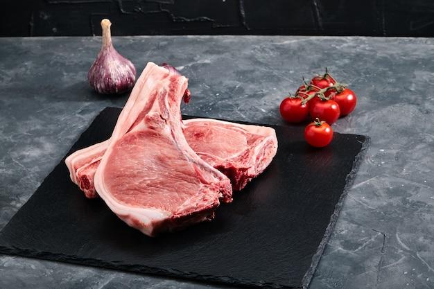 Filet de porc à l'os. deux morceaux de viande de porc sur une plaque d'ardoise sur un fond gris.
