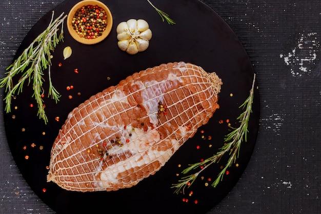 Filet de porc prêt à rôtir avec des épices sur tableau noir.