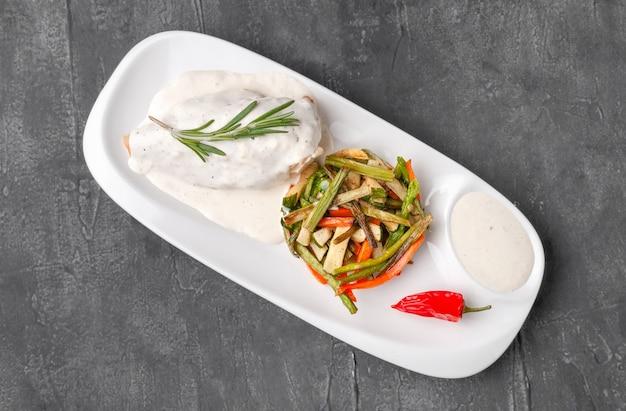 Filet de poulet au fromage mozzarella dans une sauce crémeuse aux légumes grillés sur une assiette blanche