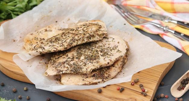 Filet de poulet aux herbes aromatiques sur parchemin sur planche de bois