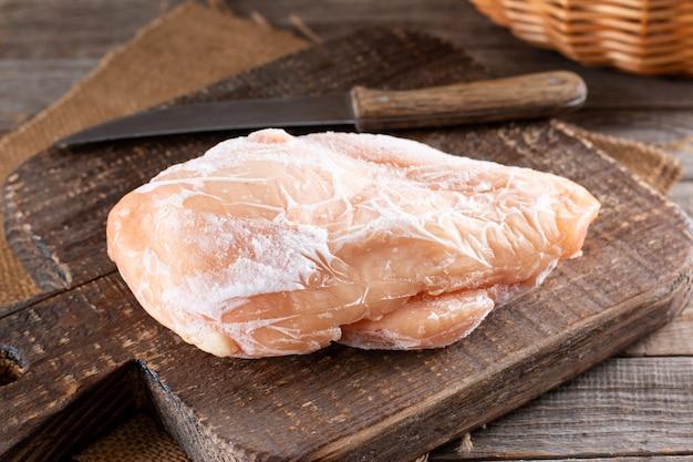 Filet de poulet congelé sur une planche à découper sur une table en bois. des surgelés