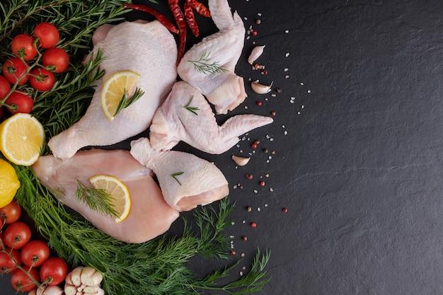 Filet de poulet cru à l'ail, poivre et romarin sur bois sur planche à découper.