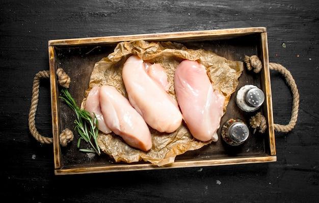 Filet de poulet cru au romarin et épices. sur le tableau noir.