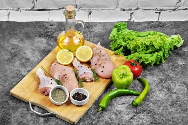 Filet de poulet cru et cuisses sur plaque en bois avec légumes frais, épices et verre d'huile.