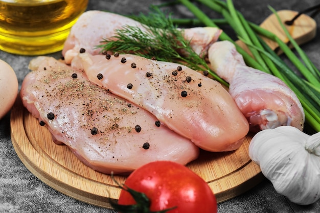 Filet de poulet cru et cuisses sur plaque en bois avec des légumes frais.