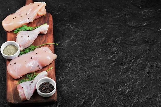 Filet de poulet cru et cuisses sur plaque en bois