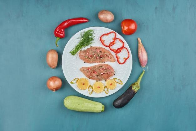 Filet de poulet cru dans une assiette blanche aux herbes et légumes.