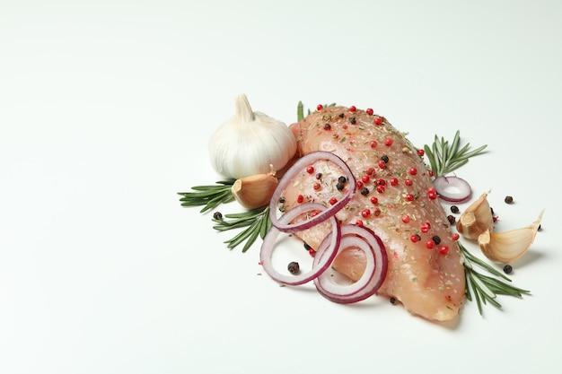 Filet de poulet cru avec des ingrédients sur fond blanc