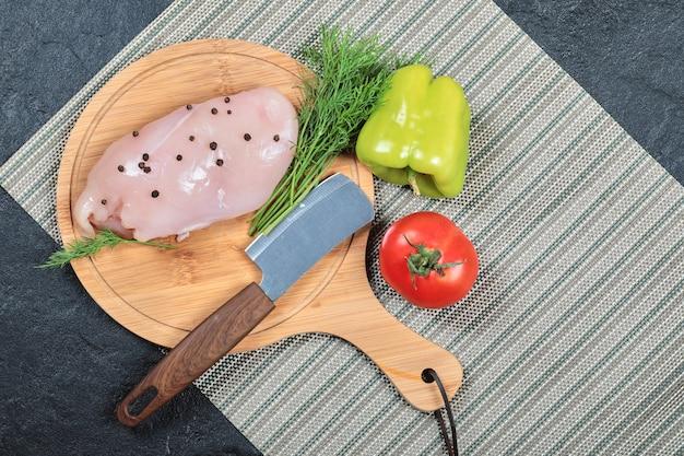 Filet de poulet cru sur planche de bois avec poivron, couteau et tomate.