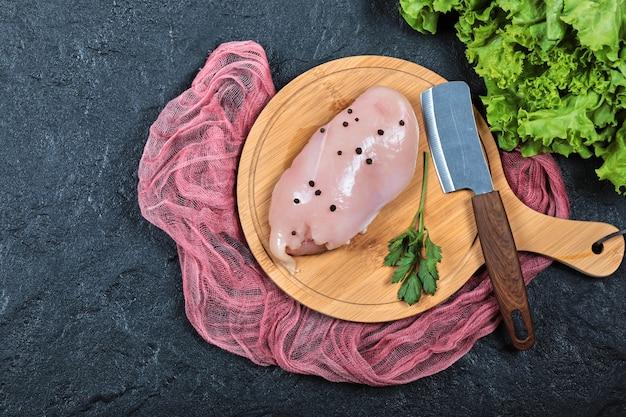 Filet de poulet cru sur planche de bois avec des verts et un couteau.