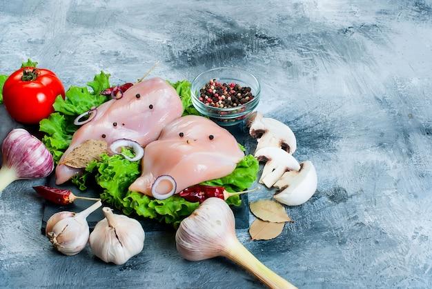 Filet de poulet cru sur une planche à découper avec des épices et des herbes.