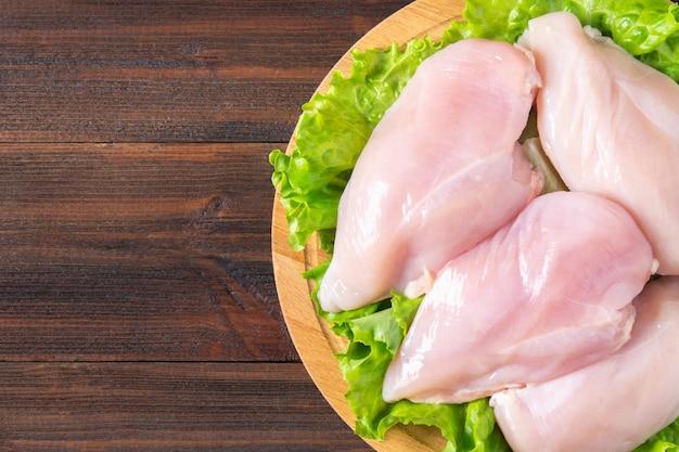 Filet de poulet cru et salade verte sur une planche à découper ronde sur un fond de table en bois.