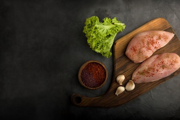 Filet de poulet cru servi avec verdure et sauces