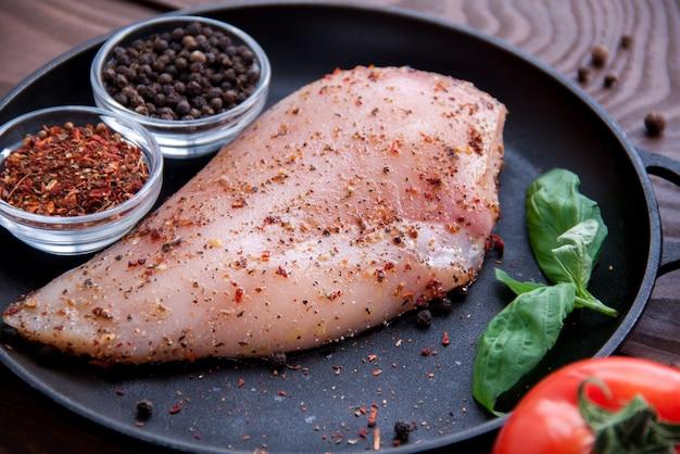 Filet de poulet frais cru aux épices et herbes se trouve sur une poêle en fer noir
