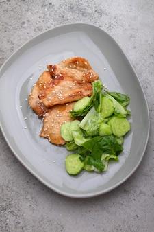 Filet de poulet frit à la sauce soja sur une assiette décorée de graines de sésame et salade verte, vue du dessus.