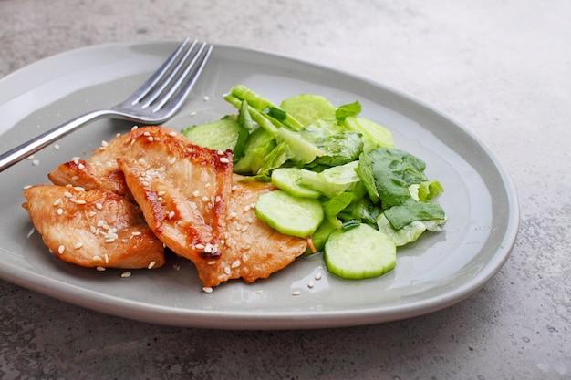 Filet de poulet frit à la sauce soja sur une assiette décorée de graines de sésame et salade verte.