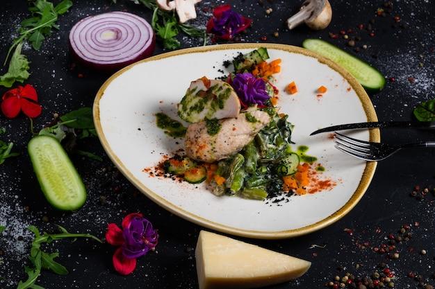Filet de poulet grillé au milieu avec mozzarella et tomates, sur un oreiller de haricots verts et épinards à la crème sur une surface sombre