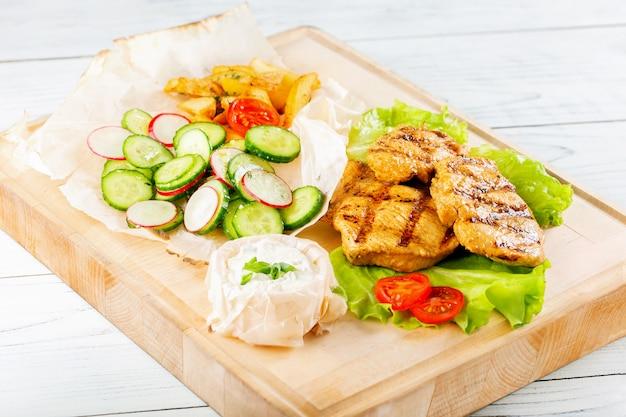 Filet de poulet grillé sur planche de bois avec des légumes. délicieuse poitrine de dinde rôtie.