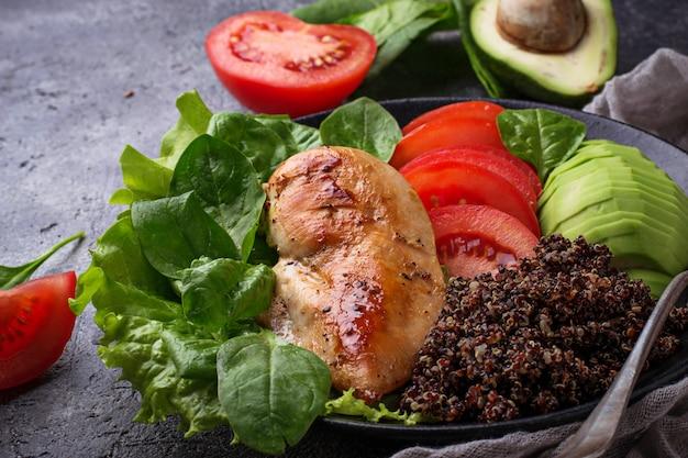 Filet de poulet grillé avec quinoa noir, salade, tomates et avocat. alimentation saine et équilibrée