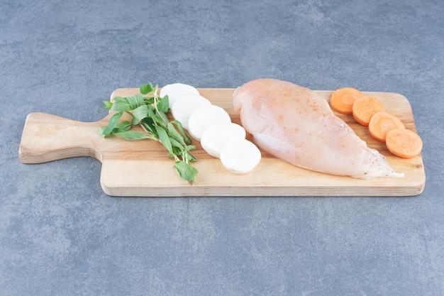 Filet de poulet non cuit aux légumes sur planche de bois.