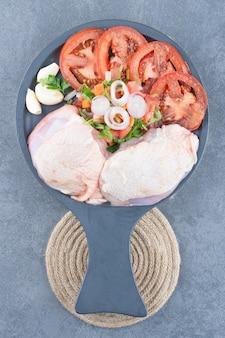 Filet de poulet non cuit avec des tranches de tomates sur une planche noire.