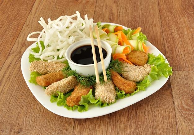 Filet de poulet pané et sésame avec nouilles de riz sautées aux légumes