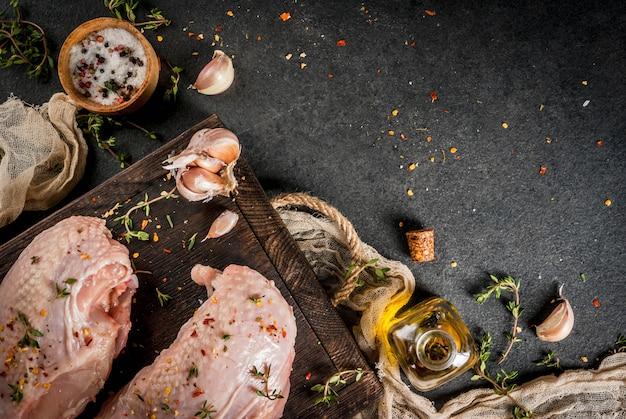 Filet de poulet avec peau sur une planche à découper aux épices