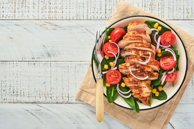 Filet de poulet avec salade d'épinards, tomates cerises, bleuet et oignon. nourriture saine. régime céto, concept de déjeuner diététique. vue de dessus sur fond blanc.