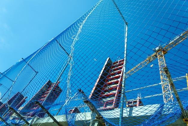 Filet de protection sur un chantier de maçonnerie lors de la construction des piliers d'un bâtiment
