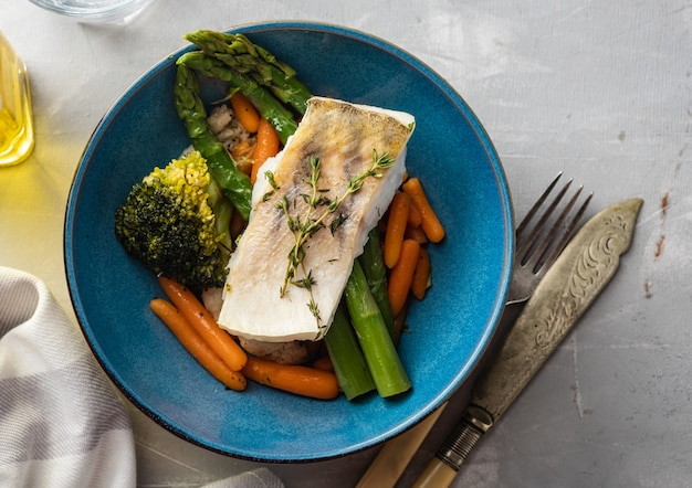 Filet de sandre aux asperges, brocoli et carottes. poisson frit avec des légumes verts cuits
