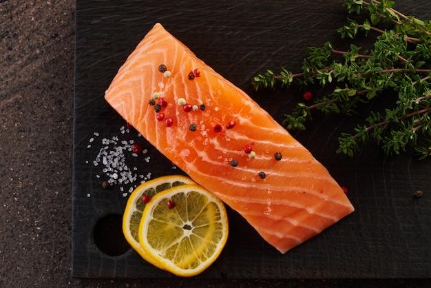 Filet de saumon et assaisonnement sur planche à découper en bois foncé sur table marron
