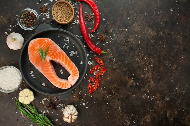 Filet de saumon aux herbes aromatiques, épices et légumes sur fond sombre. concept de cuisine. contexte culinaire. fond de nourriture. équilibre alimentaire sain. menu d'arrière-plan du tableau. espace de copie.