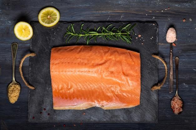Filet de saumon cru sur une assiette en ardoise noire et ingrédients pour la fabrication du gravlax.