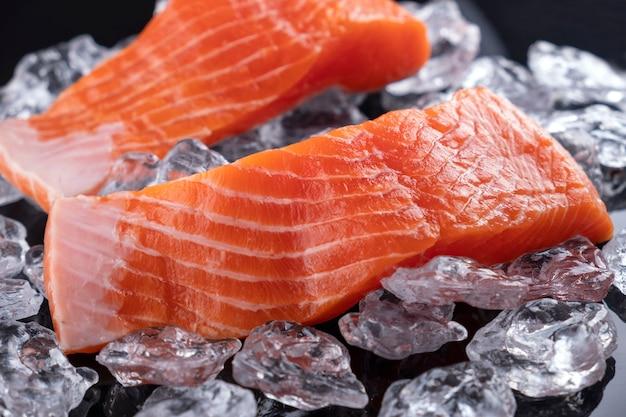 Filet de saumon cru dans de la glace sur une surface sombre. fermer
