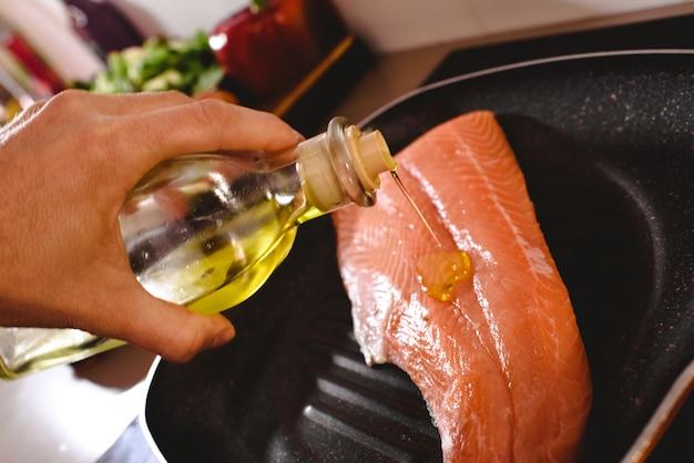 Filet de saumon cru dans la poêle, faites cuire en versant de l'huile d'olive dessus pour le faire cuire.