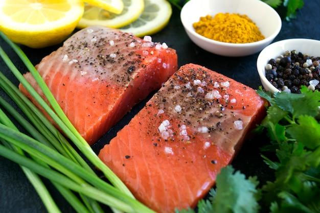 Filet de saumon cru et ingrédients pour la cuisson sur un fond sombre dans un style rustique. vue de dessus