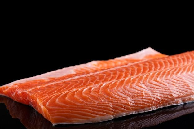 Filet de saumon cru isolé sur une surface sombre.