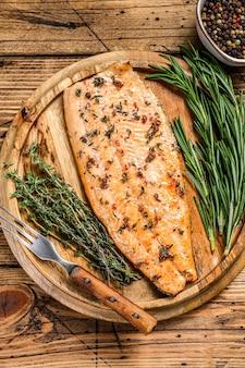 Filet de saumon cuit aux herbes et poivre rose. table en bois. vue de dessus.