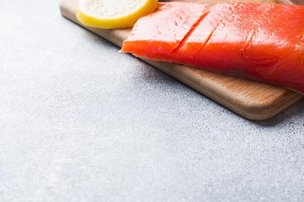 Filet de saumon frais au citron sur une planche à découper.