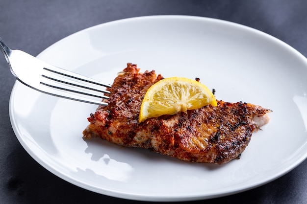 Filet de saumon frais grillé avec une rondelle de citron juteux sur une assiette blanche